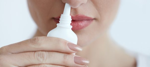 Nasal spray held up to nose