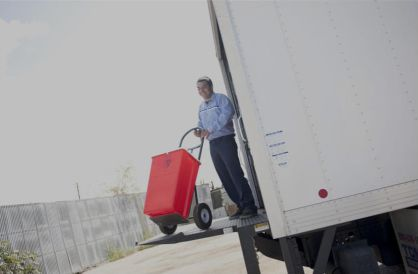 MedWaste driver rolling biohazardous waste onto a service truck