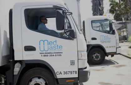 Two MedWaste service trucks with a MedWaste driver inside